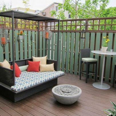 Diseño de una terraza pequeña y acogedora, cuenta con una estructura de mueble con techo con algunos cojines de colores que combinan con el color de las velas de la decoración, cerca a ellos una fuente que se puede usar como chimenea (Busybee Design)
