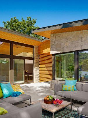 Durante el día el pino amarillo hace resplandecer la fachada, los accesos principales tienen puertas del mismo material en forma de listones horizontales