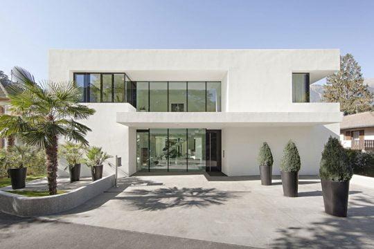 Fachada principal de la moderna casa, al centro hay un gran ventanal del hall de acceso que tiene el techo a doble altura, el techo que sobresale del primer nivel le da jerarquía al ingreso principal (Diseño: Monovolume architecture + design)