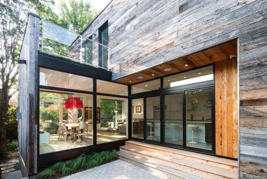 La fachada posterior de la vivienda tiene una gran área acristalada perteneciente a la zona social (sala, comedor y cocina con isla), lo que permite ganar visuales hacia el jardín