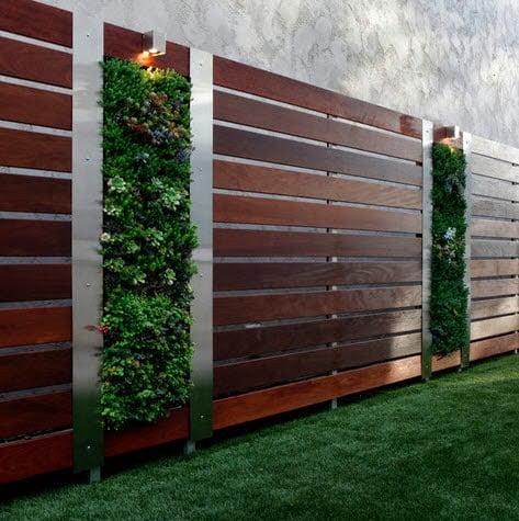 Diseño de cerco de madera que tiene como elementos decorativos espacios para plantas Foto: Better Landscape and Gardens