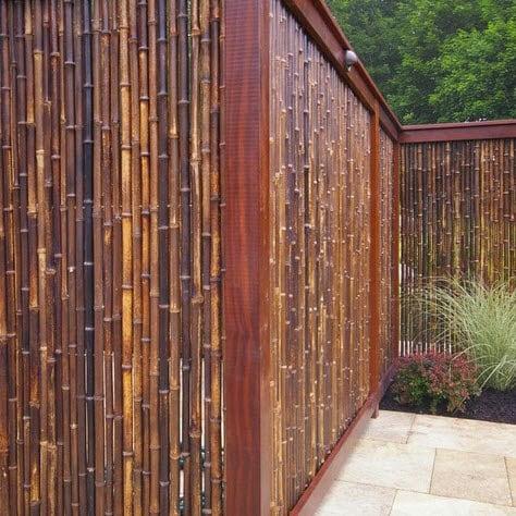Cerco de bambú oscuro y columnas de madera, se ha colocado iluminación en la parte superior Foto: Environmental Landscape Associate