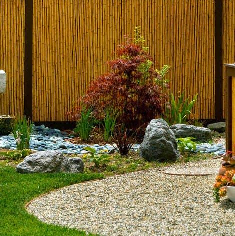 Un hermoso jardín que tiene como fondo una cerco hecho de bambú y columnas de madera pintadas en marrón Foto: Jesse Im/bugonmyleaf
