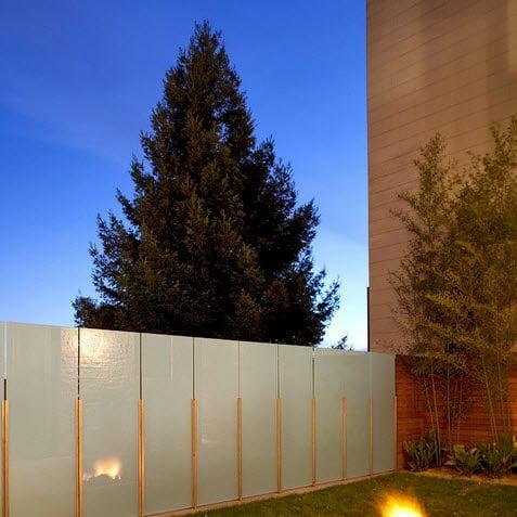 Cerco con diseño de lineas recta, tiene paneles de vidrio que permiten cortar el viento Foto: John Maniscalco Architecture