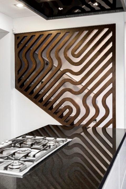 Detalle de la pared con trabajos de madera calada que divide virtualmente la cocina y la escalera