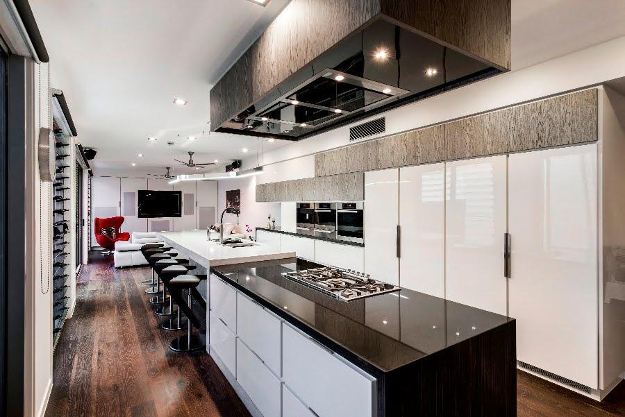 En el primer plano podemos ver la moderna cocina con isla y al fondo la sala
