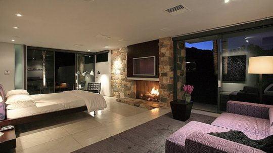 Un amplio dormitorio para un artista famoso del cine, aquí se ha colocado piedra alrededor de la chimenea dándole a este espacio un ambiente cálido