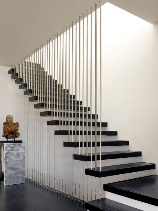 Elegante diseño de escaleras con barandas verticales de aluminio circular y tirantes de acero que combina muy bien con los peldaños pintados en color negro (Group 41 Architects)