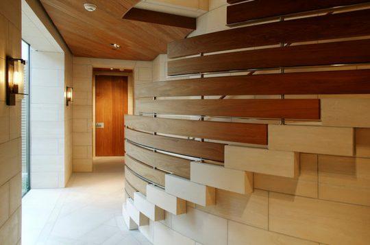Las barandas la constituyen una serie de tablones de madera que siguen la curva de la escalera  (BAR Architects)
