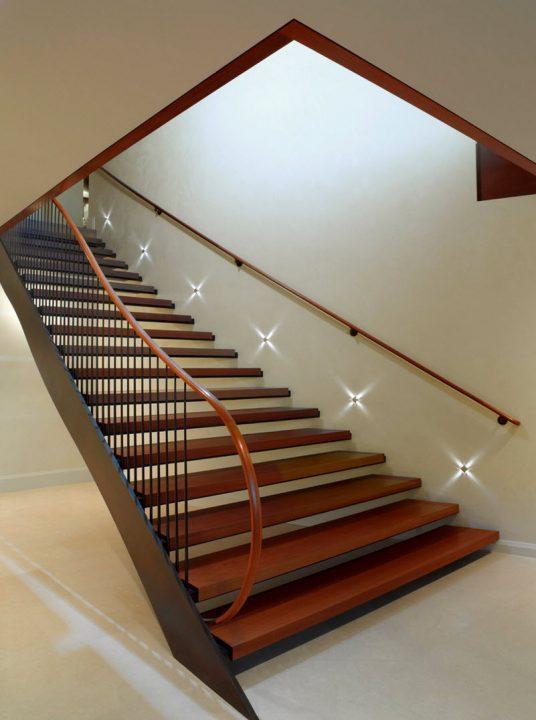Elegante y sencillo diseño de escaleras, el pasamano principal tiene forma  sinuosa con terminación semi circular (Sutton Suzuki Architects)