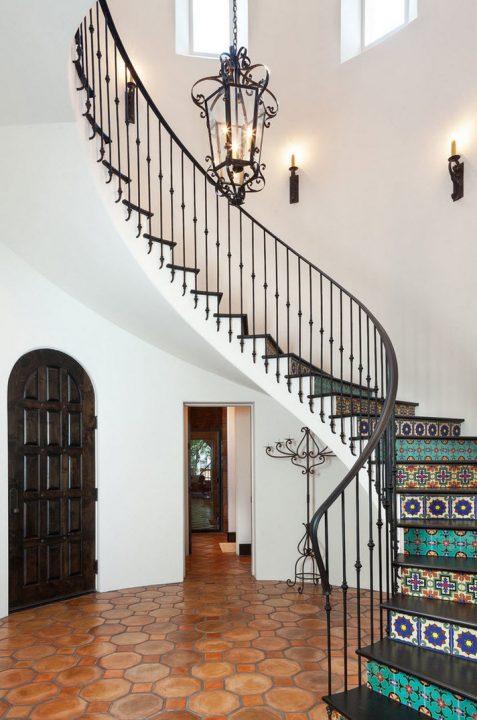 Escaleras clásicas con pasamanos de hierro decorativo, en este caso cada contrapaso se ha aplicado cerámica de diseños geométricos de múltiples colores  (Cason Graye Homes)