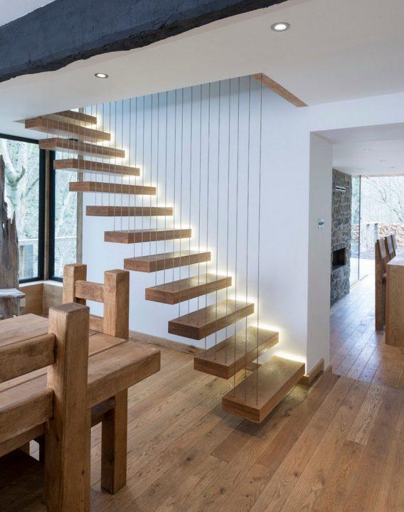 Escaleras parecen flotar con una serie de peldaños de madera y tirantes de acero que van hasta el techo, la iluminación complementa perfectamente el diseño (Heritage Doors and Floors LTD)