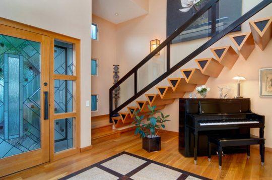 Los peldaños de la escaleras la conforman formas geométricas triangulares de madera, complementan el diseño un pasamano de hierro con vidrio templado (David Brandsen Construction)