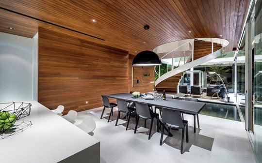 Diseño del comedor con paredes y techo enchapados en madera haciendo juego con las escaleras