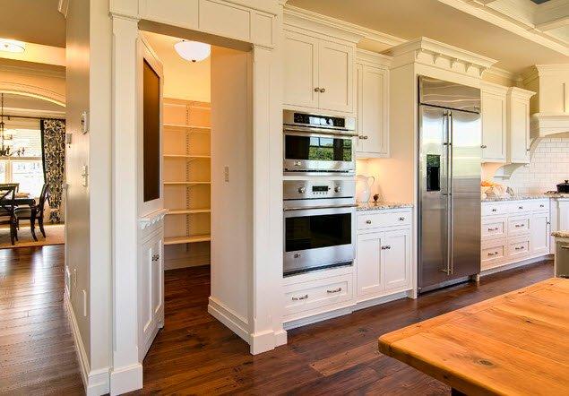 ¿Por qué diseñar una puerta común hacia la despensa de cocina si con un poco de creatividad podemos mimetizarla para hacerla parecer como parte de los muebles de cocina? (Imagen: Houzz)