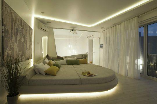 La cama ovalada parece flotar gracias al efecto de la luz que se encuentra bajo ella, aquí también se incluyó iluminación a través de ranuras de falso techo