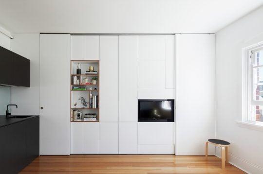 Vista del estante al frente y el mueble de cocina a la izquierda / Fotos: Katherine Lu, Diseño: Brat Swartz Architects