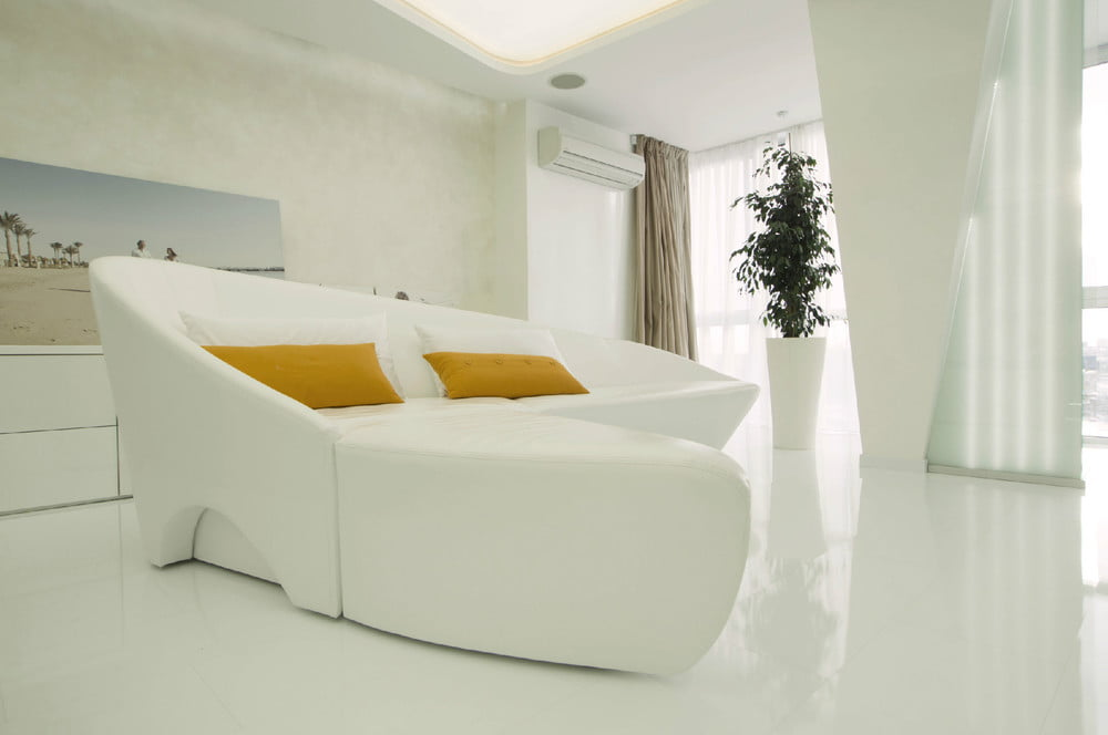Mueble de dos piezas que pueden acoplarse, cojines de diferentes tonos que contrastan con el color blanco