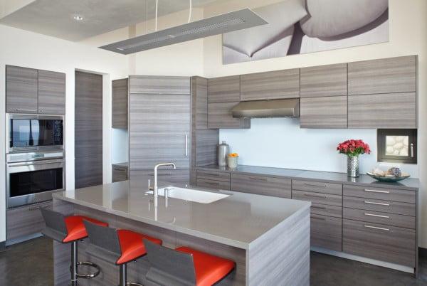 Diseño de la cocina con los taburetes tapizados de color rojo, conformando una cocina con contraste que hemos en Construye Hogar