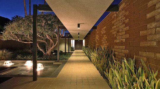 Por la noche la casa cobra vida, un largo sendero techado virtualmente nos lleva al ingreso principal mientras se disfruta de una fuente de agua iluminada
