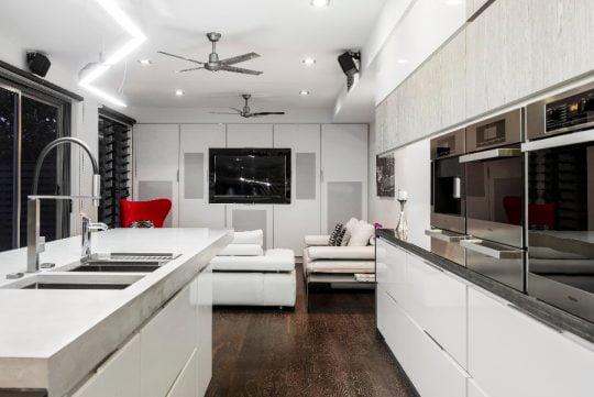 Al fondo podemos ver el diseño de la sala que tiene como punto de contraste un sofá de color rojo