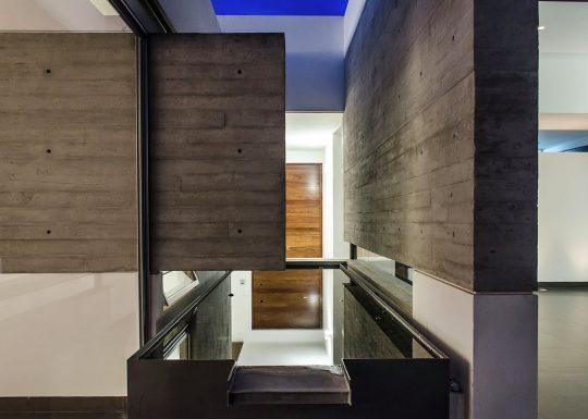 Vista del trabajo con los muros de hormigón expuestos que conectan interior con exterior (ver en planos zona de la pileta con espejo de agua)