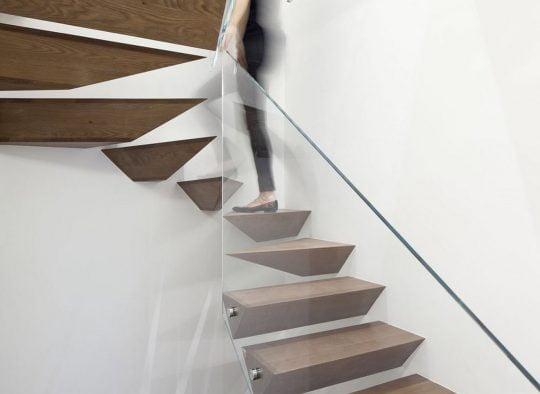 Peldaños conforman diferentes formas geométricas empotradas en la pared, cuenta con un pasamano de vidrio templado (Gerstner)