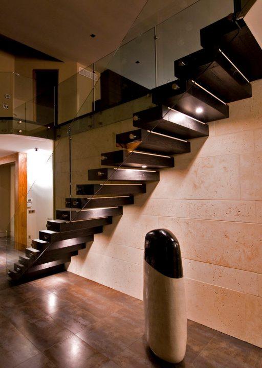Diseño de escaleras robustas con peldaños de madera que combina muy bien con la piedra aplicado -en este caso- en las paredes  (Begrand Fast Design Inc.)