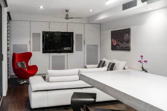 Diseño de la pequeña sala que incluye el sofá rojo haciendo contraste con toda la decoración