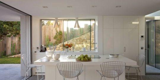 La cocina comedor luce complemente en color blanco, las sillas de metal cromado son el contraste en este diseño
