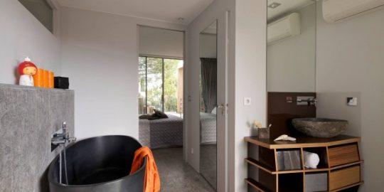 Podemos ver como el lavatorio se asemeja mucho a la piedra y descansa sobre un mueble de madera que permite guardar algunos elementos de higiene personal
