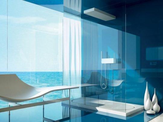 Cuarto de baño brillante con azulejos en tonos azules y cristales transparentes, complementan el moderno diseño objetos decorativos