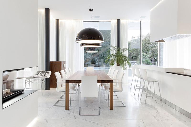 Diseño del moderno comedor que recibe abundante luz natural a través de las ventanas y decorativa en los falsos techos y debajo de algunos muebles