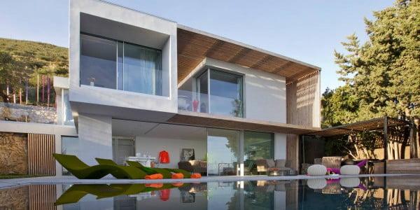 La fachada de la casa de dos pisos es simétrica, pero destaca el techo virtual de madera al lado derecho que le da personalidad y estilo a esta vivienda unifamiliar