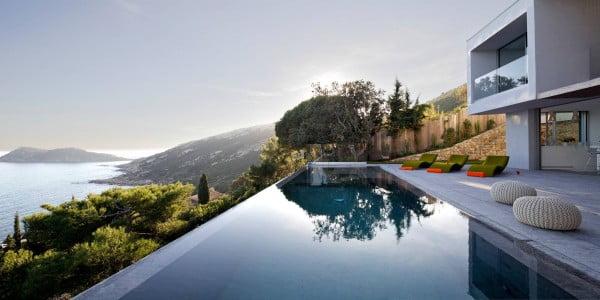 La piscina luce hermosa con el nivel del agua al ras del muro que también funciona como un espejo de agua de día y de noche