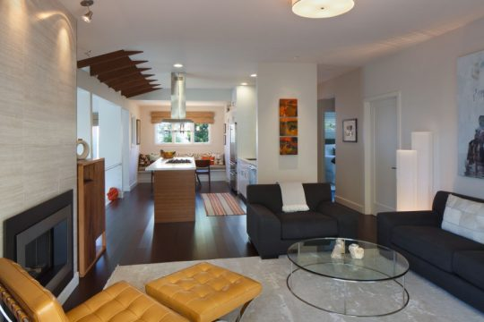 En el primer plano podemos ver el diseño de la sala, al fondo la cocina lineal