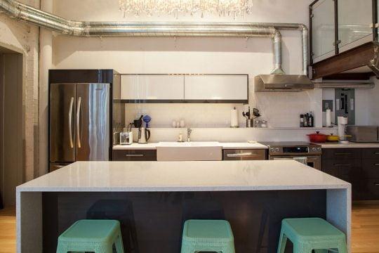 La cocina es minimalista y como no podía ser de otra forma en este tipo de decoración los tubos plateados  de la campana extractora están expuestos,  así como las demás tuberías del apartamento