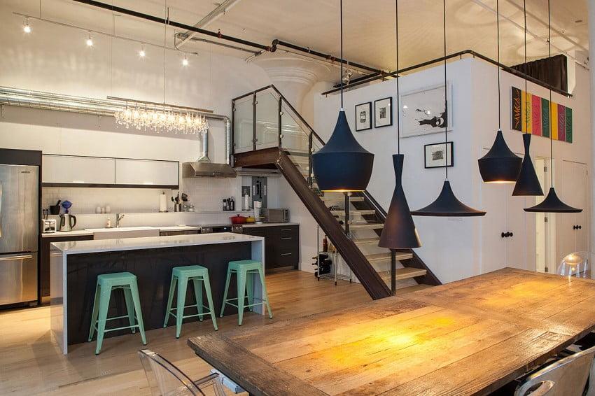 En el diseño de interiores del apartamento estilo industrial destaca el uso de creativas lámparas de techo, como las que vemos sobre la isla de cocina y sobre la mesa del comedor