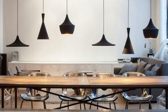 Juego de lámparas colgantes en color negro de diferentes formas que están dirigidas directamente sobre la mesa de comedor le dan un toque especial al área