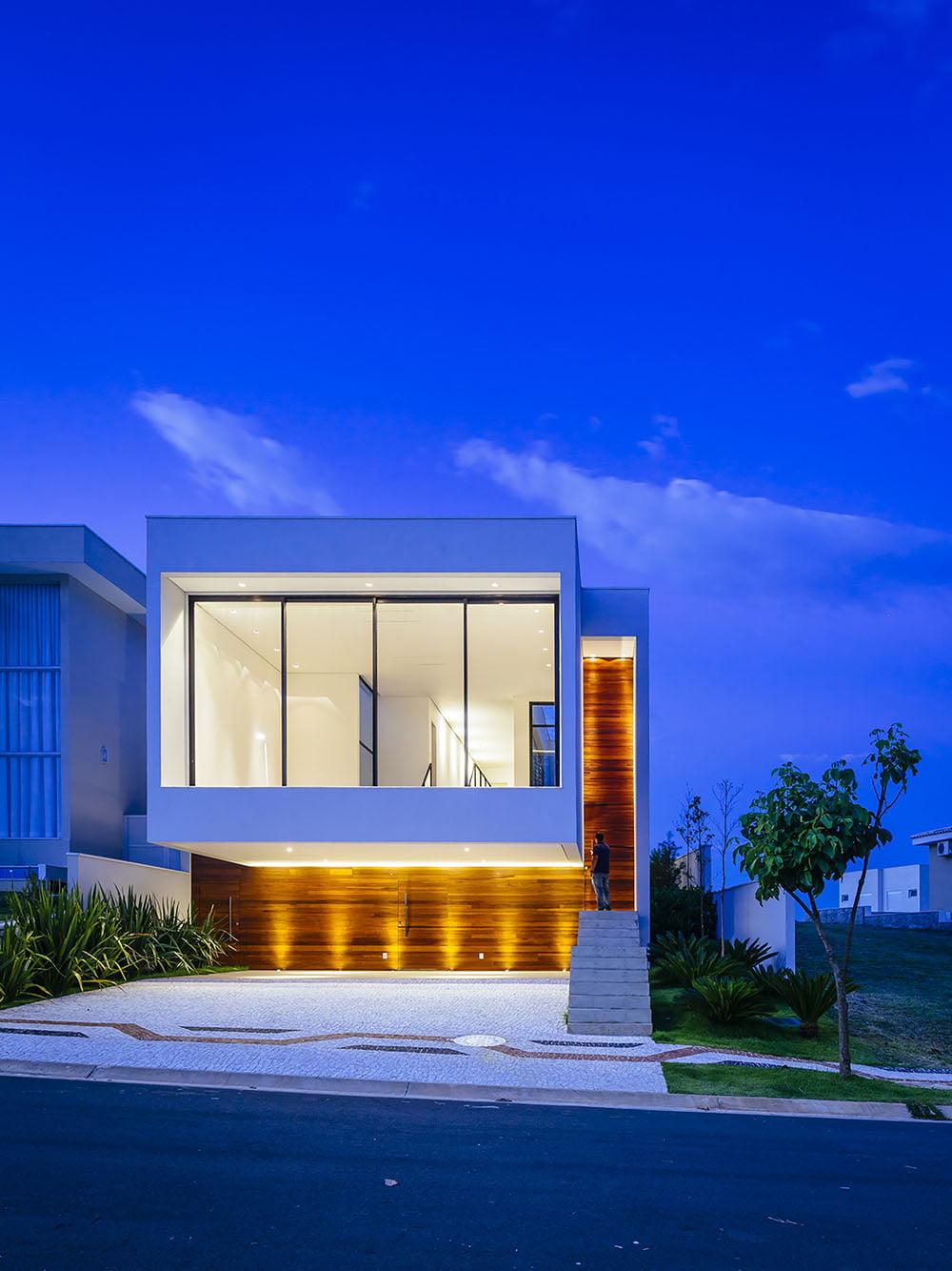 La fachada tiene una interesante iluminación desde el suelo lo que permite resaltar las texturas y color de la madera por la noche