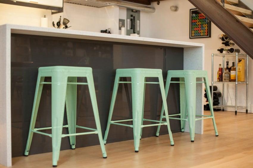 Sencillos bancos en tonos de color verde se han colocado en la isla de la cocina del apartamento