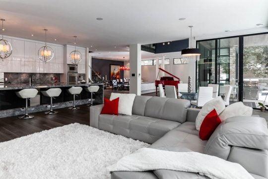 En el primer plano podemos ver el juego de muebles de la sala y al fondo la cocina con cuatro taburetes
