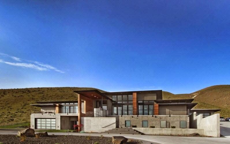 Hermosa fachada de la casa en la montaña, se puede ver el concreto pulido en acabados que entona con el entorno