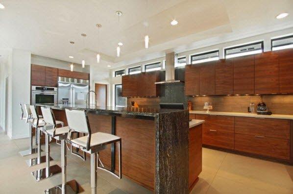 Los taburetes son de acero y combinan muy bien con la madera y la isla de la cocina