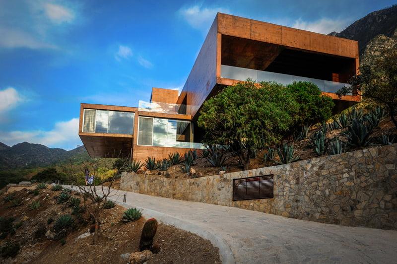 Ingreso principal a la moderna vivienda que luce imponente con los volúmenes que parecen sobresalir entre los árboles del cerro (Diseño: David Pedroza Castañeda )