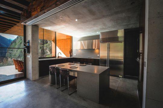 Diseño de isla de cocina en concreto y uso de cromados en la cocina