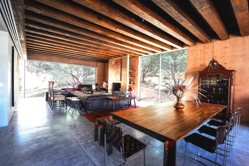 El techo con vigas de madera representa un punto fuerte de la decoración de interiores, en la foto se complementa muy bien con la mesa del comedor