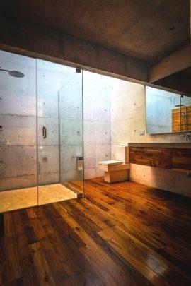 Diseño del amplio cuarto de baño, el piso aquí es de madera sin embargo tanto las paredes como el techo tienen el concreto expuesto